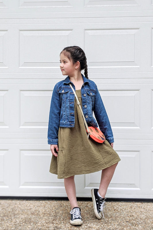 Child stands in front of white background wearing a Mini Marcel sundress, jean jacket, round purse, and converse shoes.