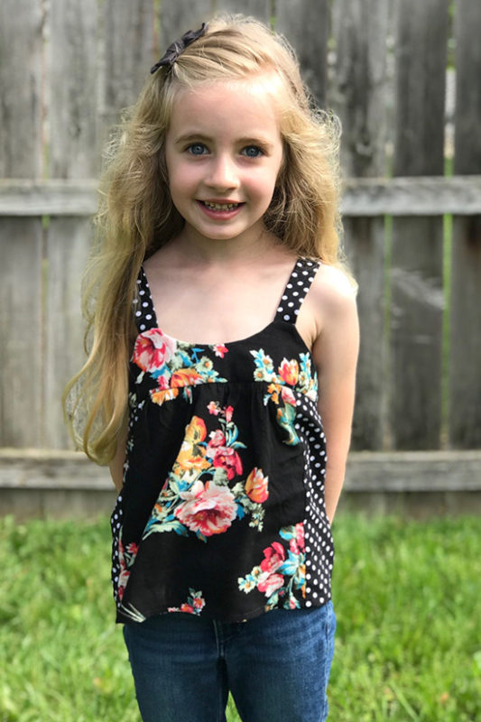 child stands in front of fence wearing a black floral and polka dot Mini Marcel tank top.