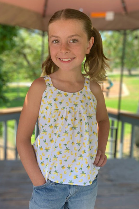 Child wears a Mini Marcel tank top in a white fabric with lemon print.