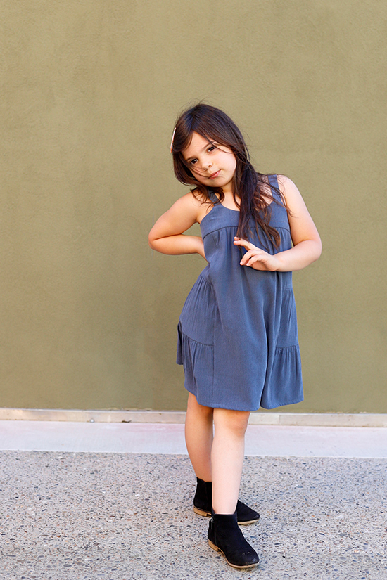 Child stands in front of green wall wearing a blue mini length Mini Marcel Dress