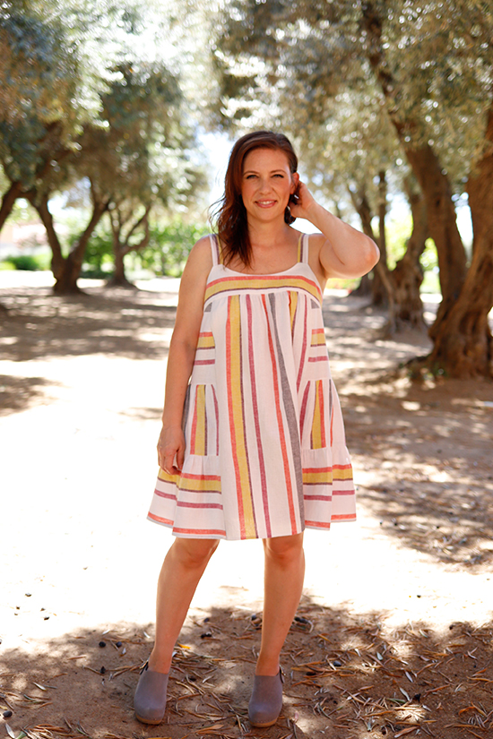Woman wearing striped mini length Marcel Dress stands in front of trees