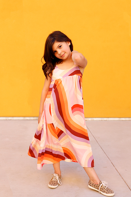 Child stands in front of yellow wall wearing a midi length Mini Marcel Dress