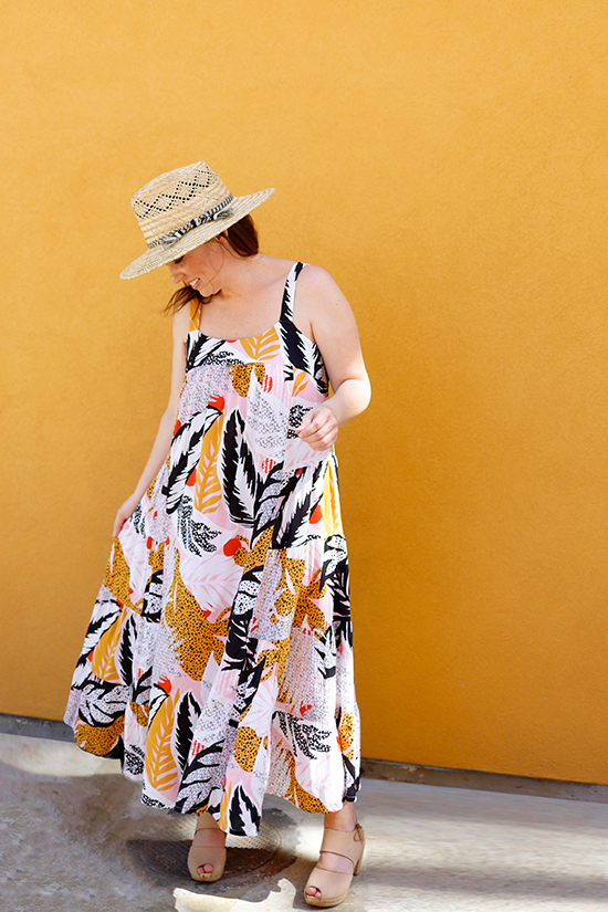 Woman in front of yellow wall wears a Midi length Marcel Dress