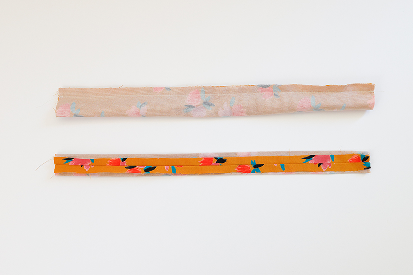 Two Marcel pattern strap pieces are shown against a white background. One is folded lengthwise with stitching across the top. The other is turned right side out and pressed flat with the seam centered.