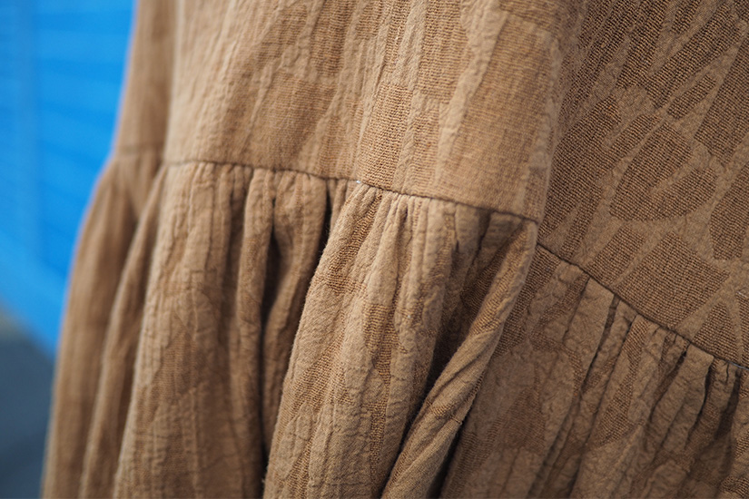 Close up view of gathered caramel colored slub texture fabric