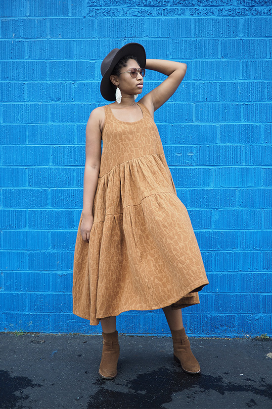 Woman standing in front of blue wall has hand on head and is wearing a caramel colored tiered dress which is blowing in the wind.