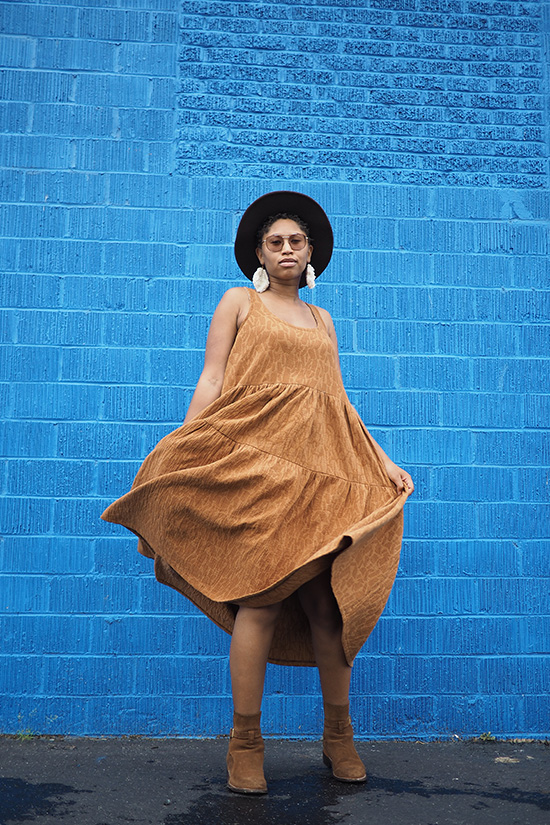 Woman wearing a caramel colored tiered dress twirls in front of a blue wall.