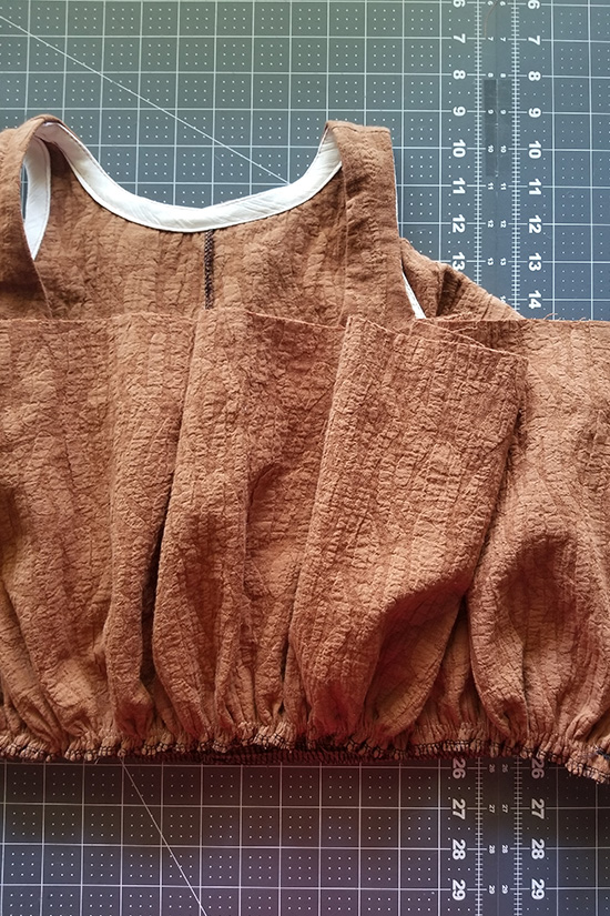First tier caramel colored dress is placed right sides together with the bodice and stitched.