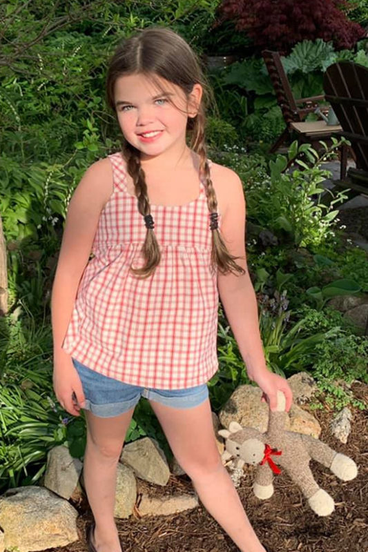 Child stands in front of greenery wearing a red plaid Mini Marcel tank top.