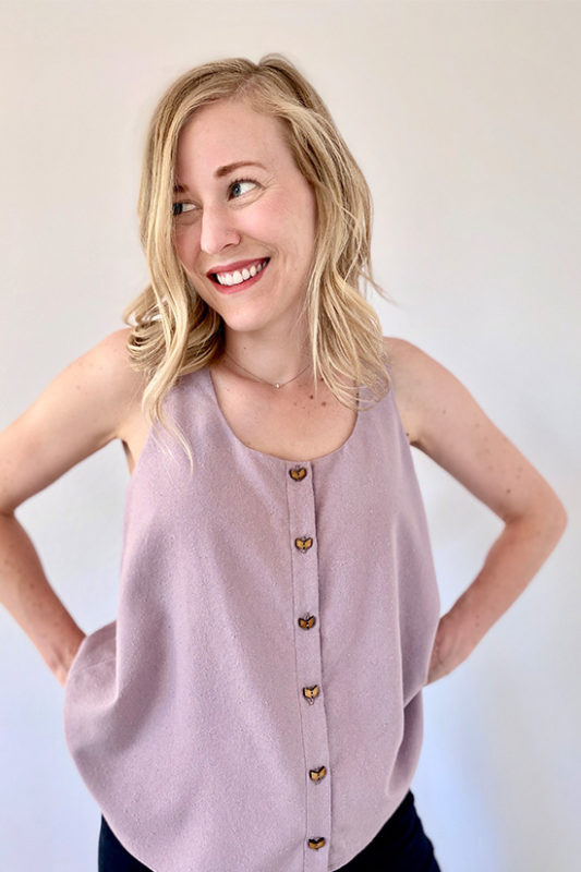 Woman wearing light purple tank top with wooden buttons down front.