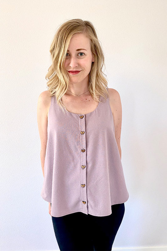 Woman wears light purple swing tank with wooden buttons down front