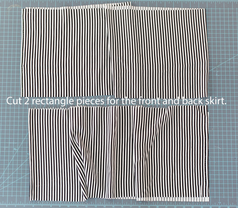 Two rectangles of black and white striped fabric lay on a cutting mat background.