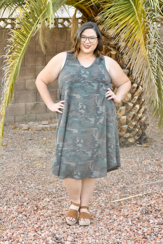 Woman stands while wearing knee length Pony Tank dress in camo fabric.