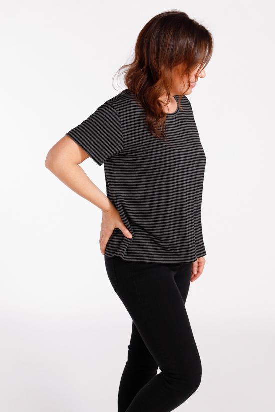 Woman wearing a black tee with white stripes stands in front of white background.