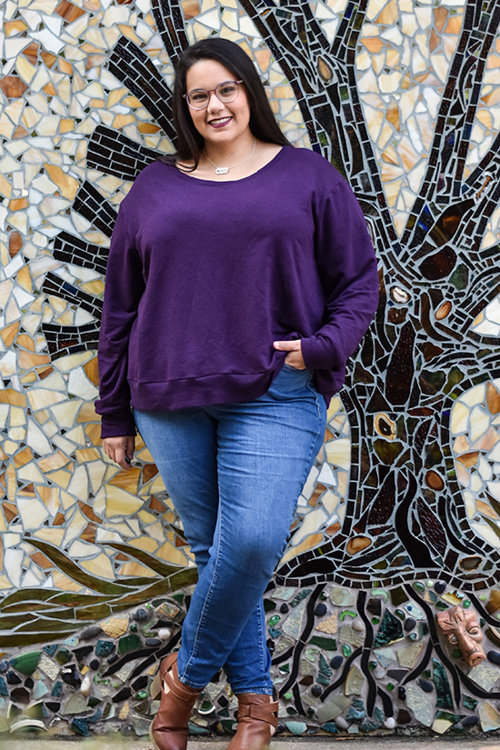 A woman wearing a purple long sleeved Pixie Tee stands in front of a mosaic wall.