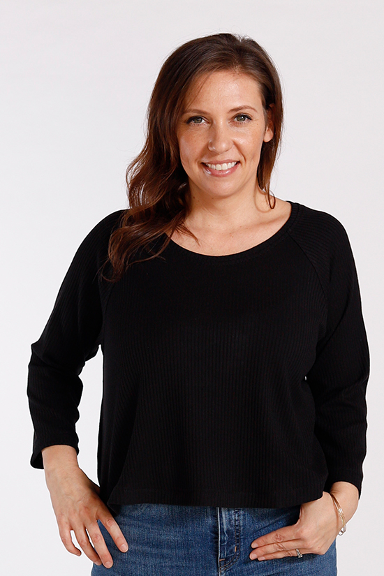 Gabriela wears a cropped black Waterfall Raglan while standing in front of a white background.