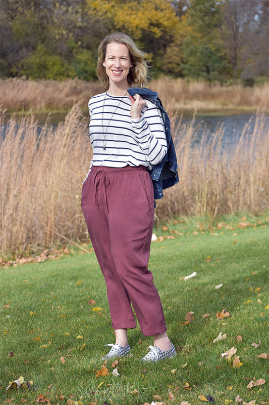 Woman wearing striped tee and burgundy elastic waist Crew trousers shown standing on grass.