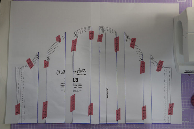 Orchid puff sleeve pattern pieces are spread apart and taped to paper underneath.