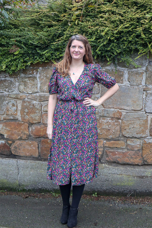 Woman wears floral puff sleeve orchid midi dress while standing in front of stone wall.