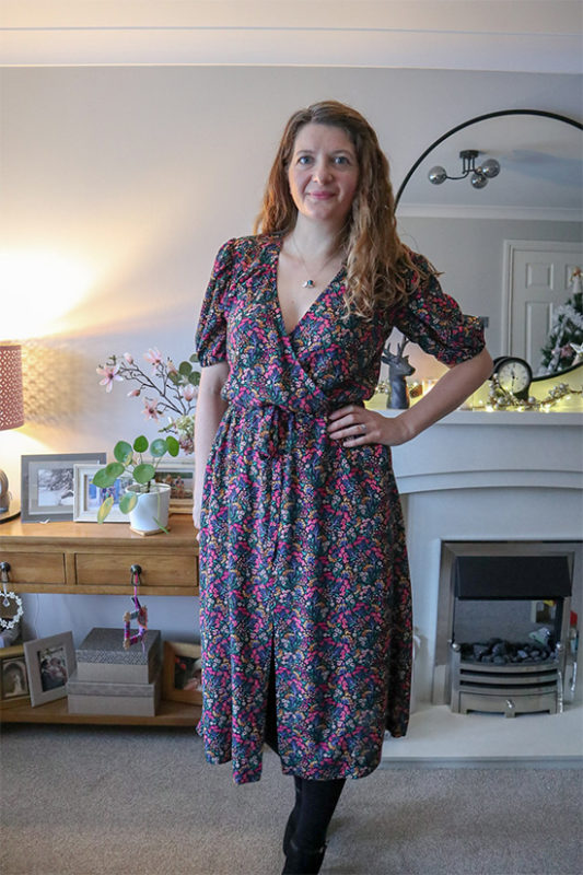 Woman stands while wearing a floral print puff sleeve orchid midi dress.