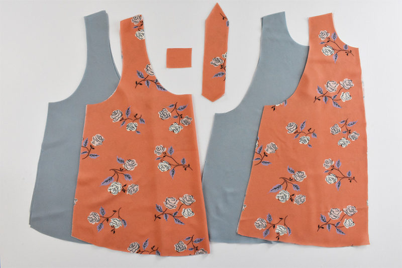 Blue and coral fabrics cut into Victory Tank pattern pieces