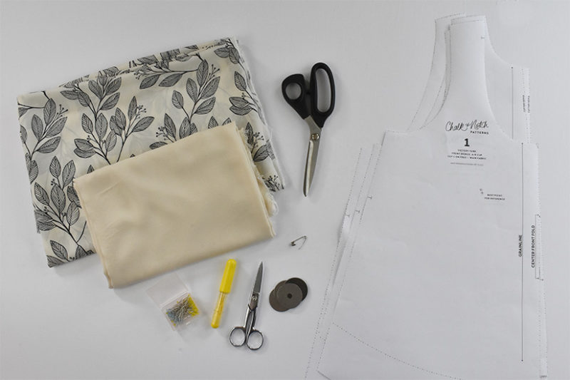 Fabric, scissors, pins, marking tools, pattern weights, and paper pattern pieces are laid on a white background.