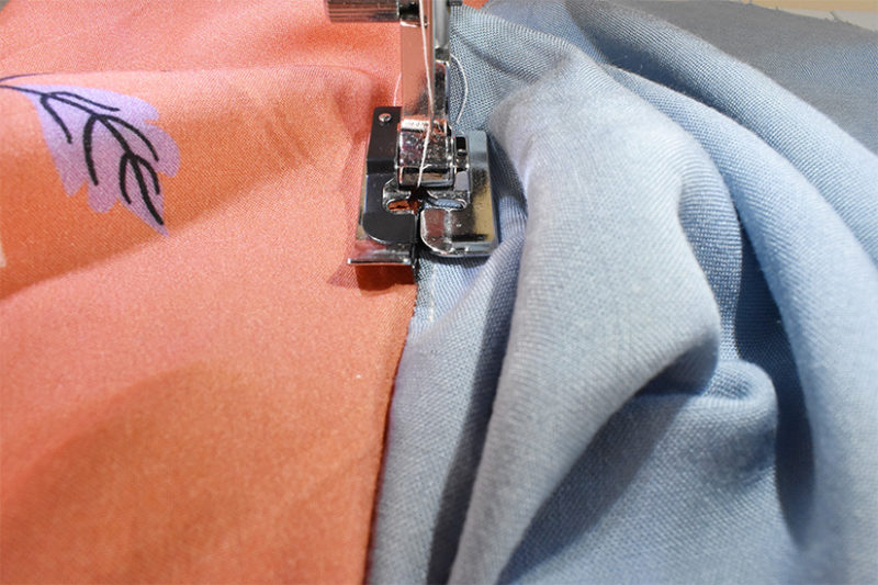 A sewing machine foot is shown understitching the lining.