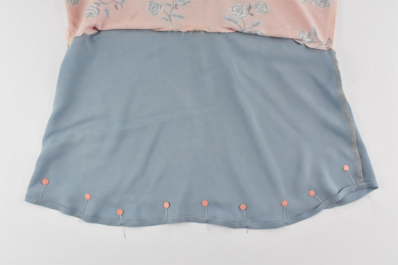 The hem of lining fabric is shown folded up and pinned.