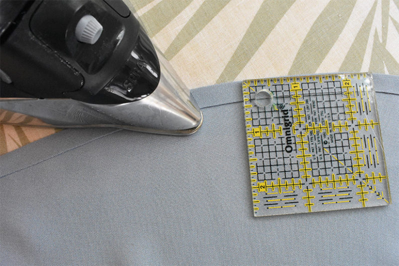 An iron and small ruler are shown on a folded fabric edge.