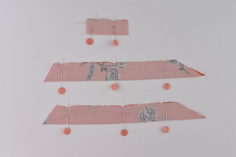 Three coral fabric strap pieces are folded in half right sides together and pinned.
