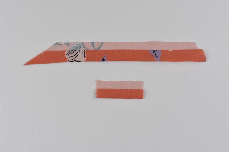 Coral fabric strap pieces are shown folded in half lengthwise with one edge folded again.