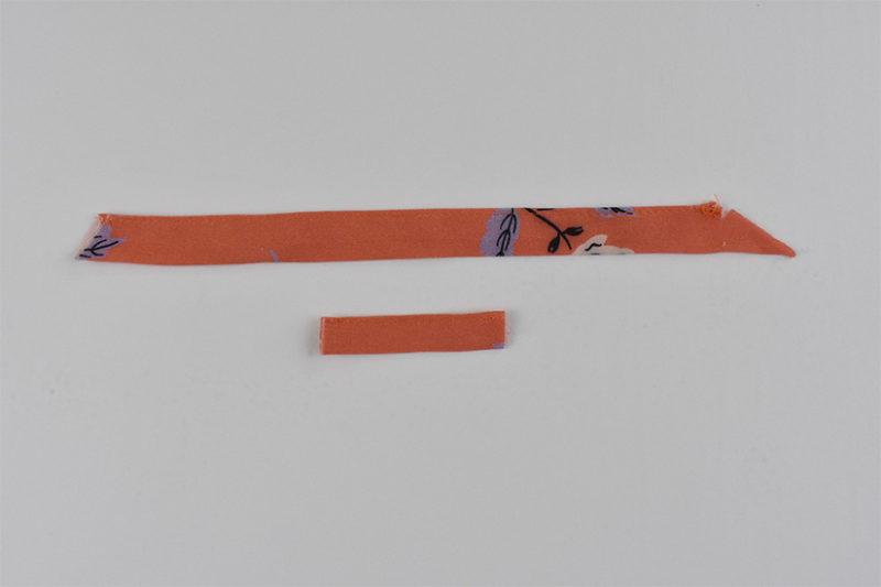 coral fabric straps are shown sewn closed.