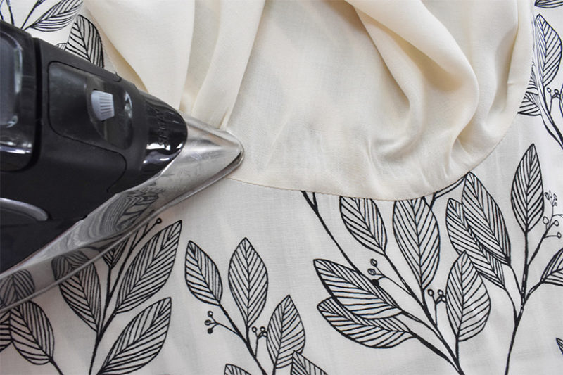An iron presses the seam allowance towards the cream lining and away from the black and white main fabric.