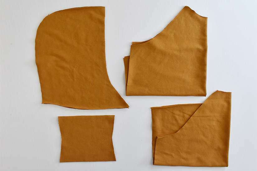 Gold colored fabric is cut into pieces for a page hoodie.