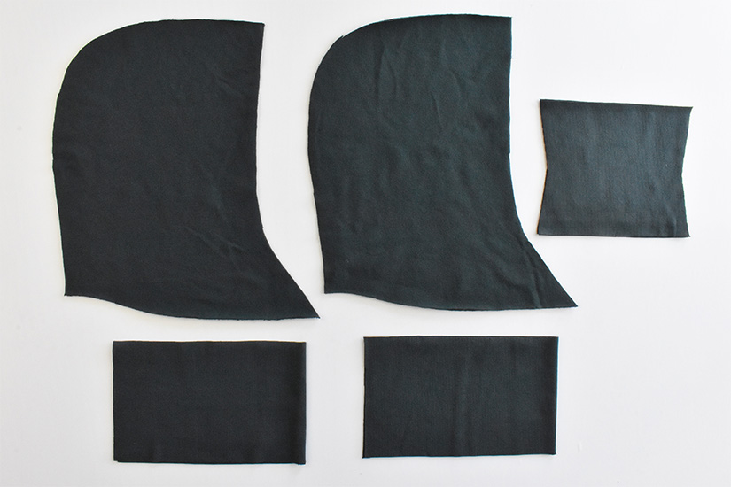 Dark green/blue fabric pieces are cut for the page hoodie.