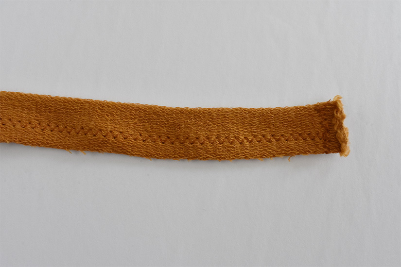 Stitching is shown along the bottom of a strip of yellow knit fabric