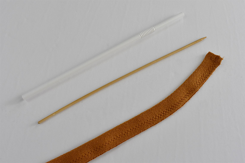 A straw, wooden stick, and sewn strip of yellow fabric lay on a white background