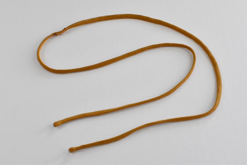 Two yellow fabric strips are sewn together into one long drawstring.