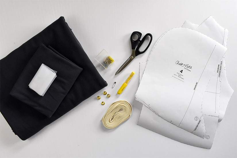Dark colored fabric, pins, and paper Page Hoodie pattern pieces are shown on a white background.