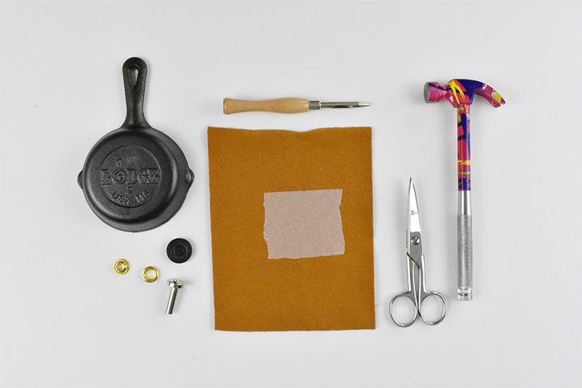 A small cast iron skillet, grommets, an awl, yellow fabric, interfacing, scissors, and a small hammer are arranged on a white background