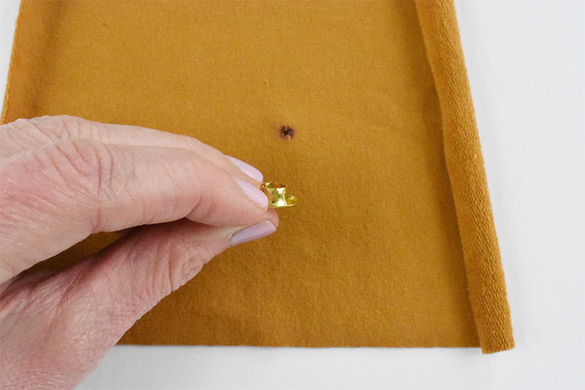 A brass colored grommet piece is held above a small hole cut into a yellow knit fabric