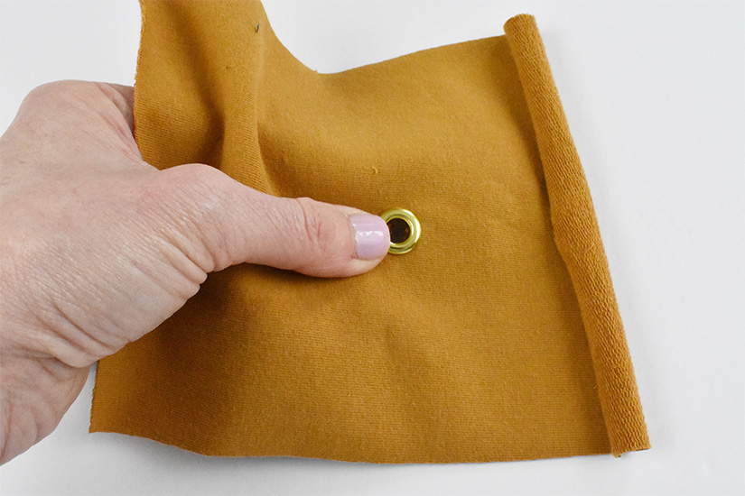 The top piece of a grommet is inserted into a small hole in yellow knit fabric.
