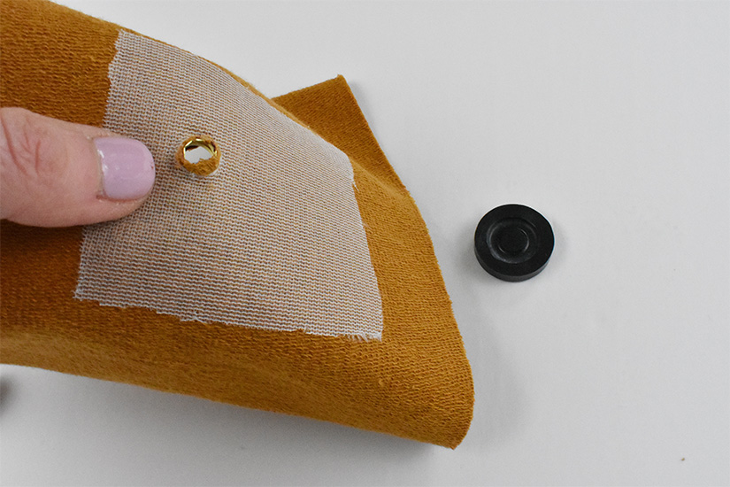 The back side of yellow knit fabric with the top grommet inserted is shown.
