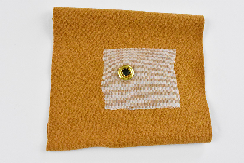The bottom part of a brass grommet is positioned over a hole on the wrong side of yellow knit fabric