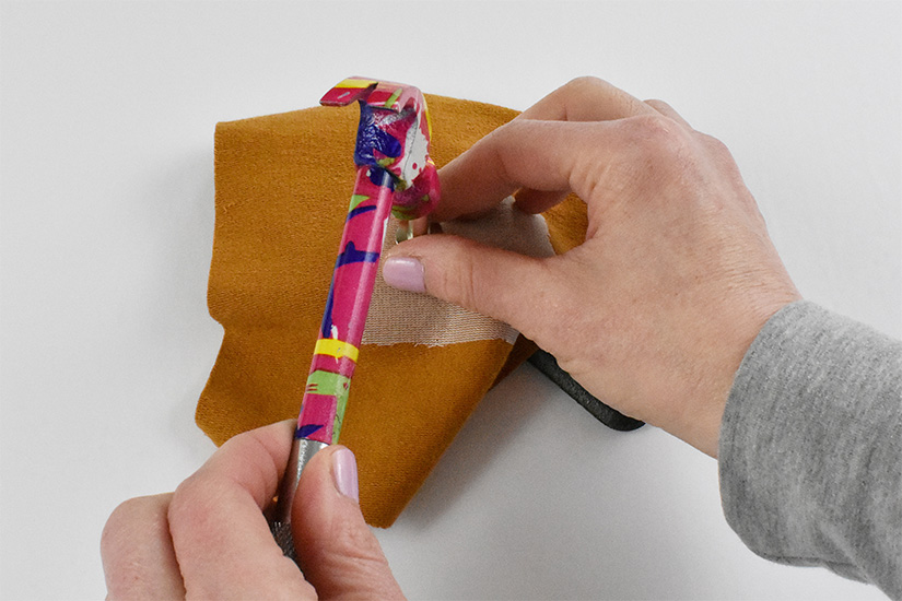 Hands hold a hammer as it hits the top of a silver setting tool placed on the grommet inserted into yellow knit fabric.