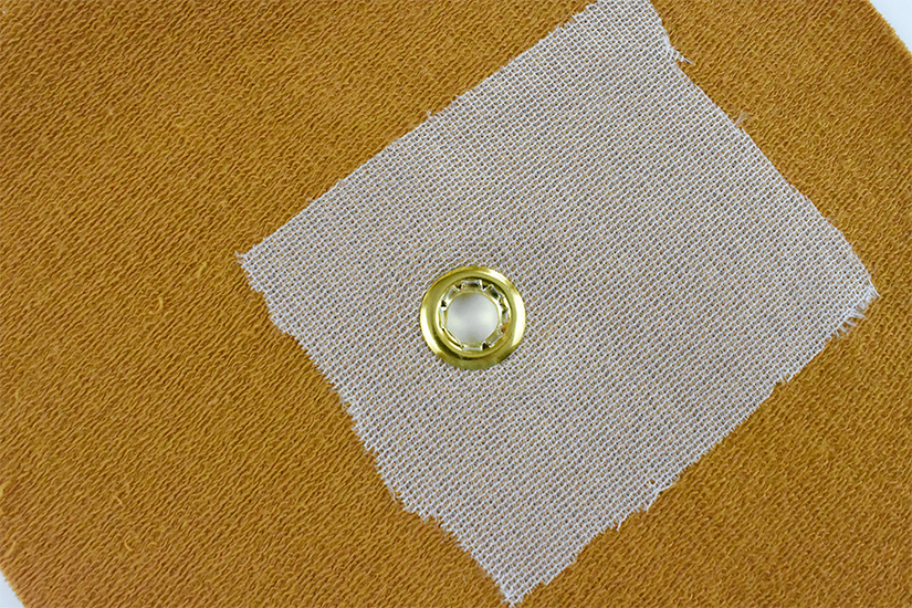 A close up of the backside of a brass grommet inserted into yellow knit fabric