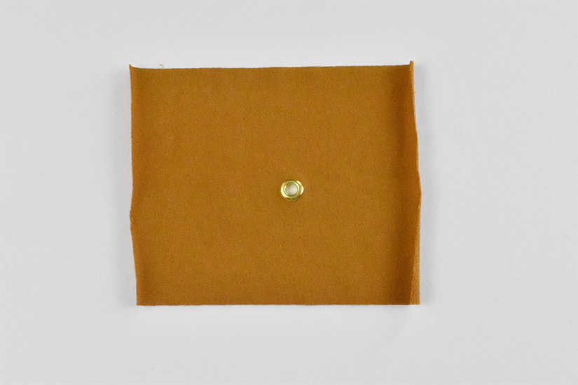 A brass grommet is shown installed in yellow knit fabric.