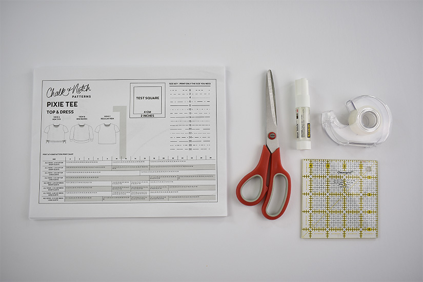 A paper sewing pattern, red scissors, a glue stick, tape, and a small ruler are shown on a white background