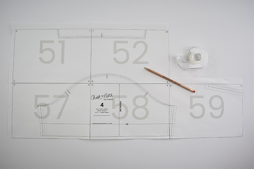 Tape, a pencil, and an assembled pdf sewing pattern sleeve piece are shown.
