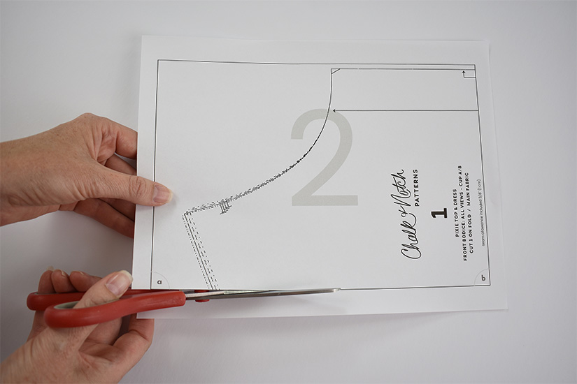 A person uses red scissors to cut along the border of a pdf sewing pattern page.